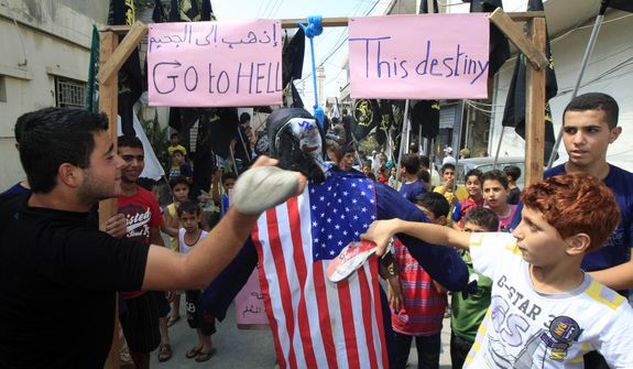 Protesters use their shoes to strike an effigy of U.S. President Barack Obama during a protest about a film ridiculing Islam's Prophet Muhammad in the Palestinian refugee camp of Ain el-Hilweh near Sidon, Lebanon, Friday, Sept. 14, 2012. (AP Photo/Mohammed Zaatari)