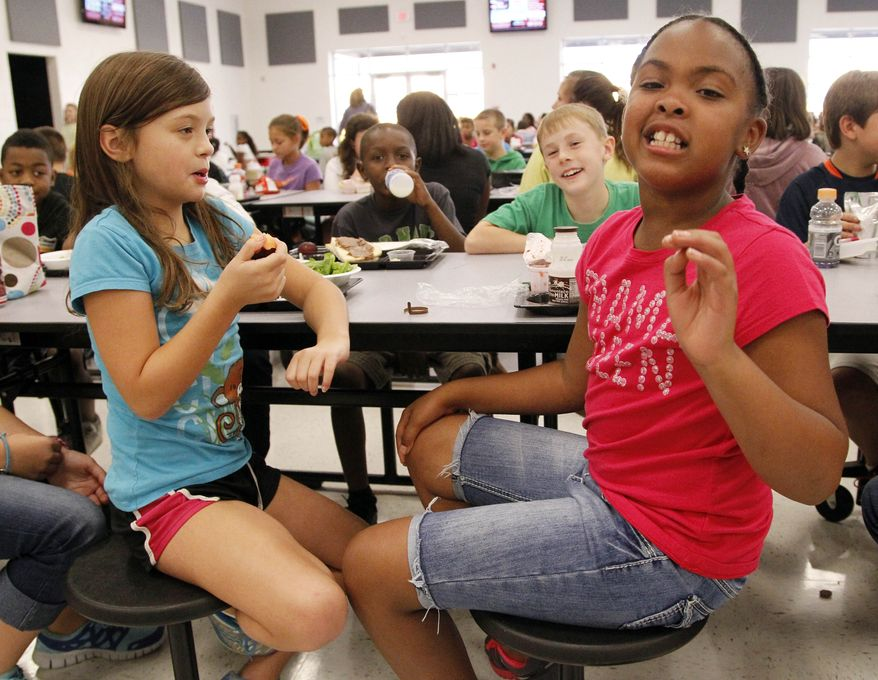 Eastside Elementary school fourth-grader Raela Bridges (right) explains what parts of the school lunch she likes to her classmates Grace Bethany (left), Cameron Kinard (back left), and Brock Maddox (back right) on Sept. 12, 2012, in Clinton, Miss. (Associated Press)