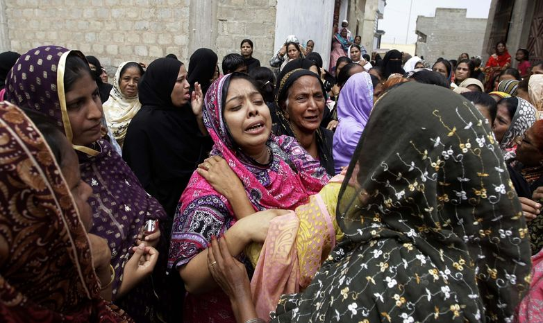 Pakistani women mourn Sept. 13, 2012, the deaths of relatives killed in a fire at a garment factory in Karachi, Pakistan. Police have opened a murder case against the factory's owners and managers for the fire, which killed hundreds of people. (Associated Press)