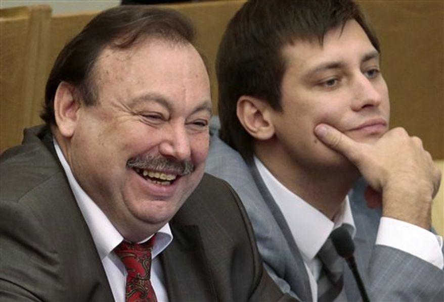 Russian opposition lawmaker Gennady Gudkov, left, and his son Dmitry react while listing during a plenary session of the State Duma, the lower parliament chamber, in Moscow, Russia, Friday, Sept. 14, 2012. Russia's lower house of parliament is voting Friday, Sept. 14, 2012, to expel Gudkov, who has angered the Kremlin with his scathing criticism and participation in opposition rallies. (AP Photo/Mikhail Metzel)