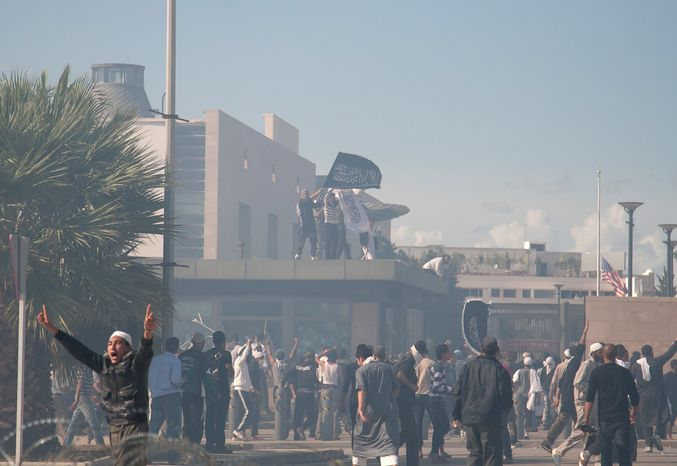**FILE** Protesters gather in front of the main entrance of the U.S. embassy, background, in Tunis, Tunisia, on Sept. 14, 2012. Thousands of demonstrators massed outside the embassy and several were seen climbing the outer wal