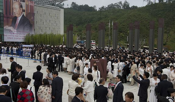 Thousands of mourners line up outside the stadium at the Cheong Shim Peace World Center in Gapyeong, Korea on Saturday, Sept. 15, 2012 for the Seonghwa, or ascension, ceremony, known as the traditional funeral in western terms, for the late Rev. Sun Myung Moon. Thousands of mourners from countries around the world came to witness the event and say goodbye to the head of the Unification Church. Some 15,000 fit into the stadium, where the funeral was held, with another 10,000 to 15,000 expected to be watching live simulcasts around the complex. (Barbara L. Salisbury/The Washington Times)