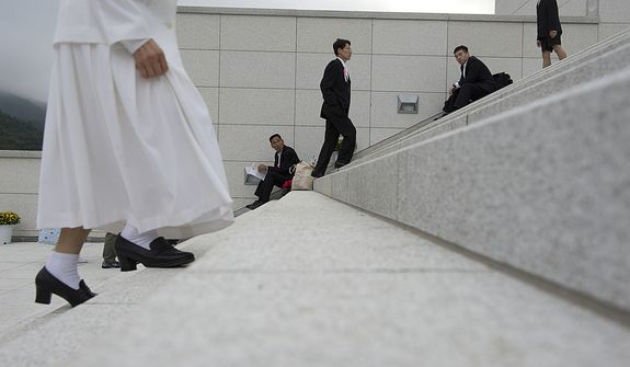 Mourners make their way up the steps while others rest on them, heading to the Seonghwa, or ascension, ceremony, known as the traditional funeral in western terms, for the late Rev. Sun Myung Moon on Saturday, Sept. 15, 2012 at the Cheong Shim Peace World Center in Gapyeong, Korea. Thousands of mourners from countries around the world came to witness the event and say goodbye to the head of the Unification Church. Some 15,000 fit into the stadium, where the funeral was held, with another 10,000 to 15,000 expected to be watching live simulcasts around the complex. Because it was first-come, first-served for many of the seats, most mourners arrived early and spent time outside on the steps. (Barbara L. Salisbury/The Washington Times)