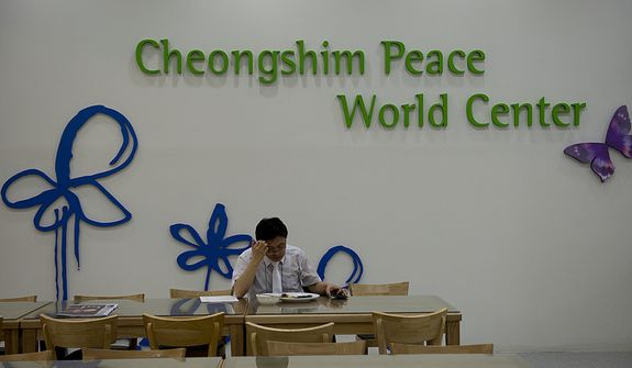 A staff member eats in the cafeteria of the Cheong Shim Peace World Center in Gapyeong, Korea before the Seonghwa, or ascension, ceremony for the late Rev. Sun Myung Moon on Saturday, Sept. 15, 2012. Although the funeral did not start until 10 a.m., mourners arrived hours in advance, so staff members had to be at the facility in the wee hours of the morning. (Barbara L. Salisbury/The Washington Times)