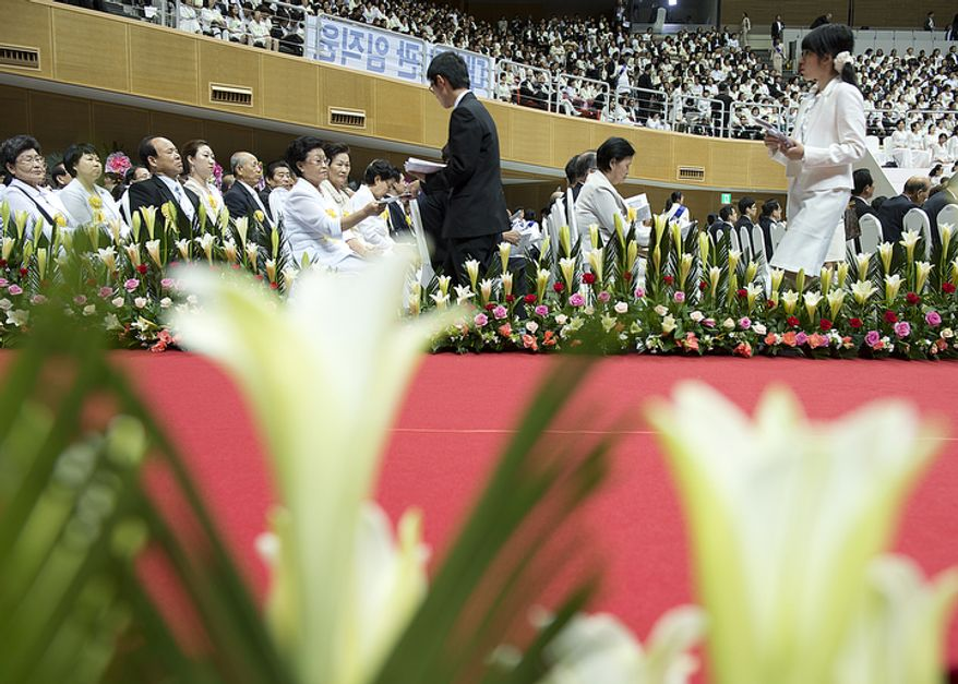 Ushers hand out programs to attendees at the Seonghwa, or ascension, ceremony, known as the traditional funeral in western terms, for the late Rev. Sun Myung Moon on Saturday, Sept. 15, 2012 at the Cheong Shim Peace World Center in Gapyeong, Korea. (Barbara L. Salisbury/The Washington Times)