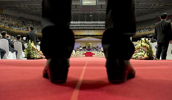 A security guard stands at the back of the stadium during a video presentation about the late Rev. Sun Myung Moon's life during the Seonghwa, or ascension, ceremony, on Saturday, Sept. 15, 2012 at the Cheong Shim Peace World Center in Gapyeong, Korea. (Barbara L. Salisbury/The Washington Times)