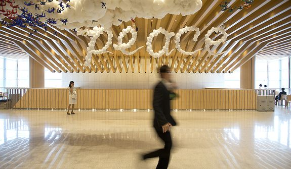 "People walk through a hallway past a ""peace"" sign that is meant to look like clouds at the Cheong Shim Peace World Center in Gapyeong, Korea on Saturday, Sept. 15, 2012, the day of the late Rev. Sun Myung Moon's funeral. (Barbara L. Salisbury/The Washington Times)"