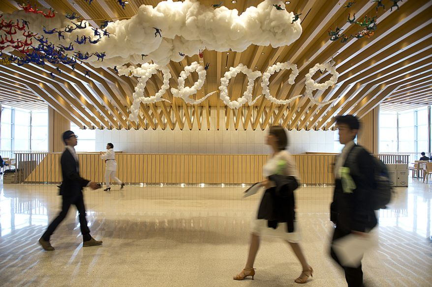 """People walk through a hallway past a """"peace"""" sign that is meant to look like clouds at the Cheong Shim Peace World Center in Gapyeong, Korea on Saturday, Sept. 15, 2012, the day of the late Rev. Sun Myung Moon's funeral. (Barbara L. Salisbury/The Washington Times)"""