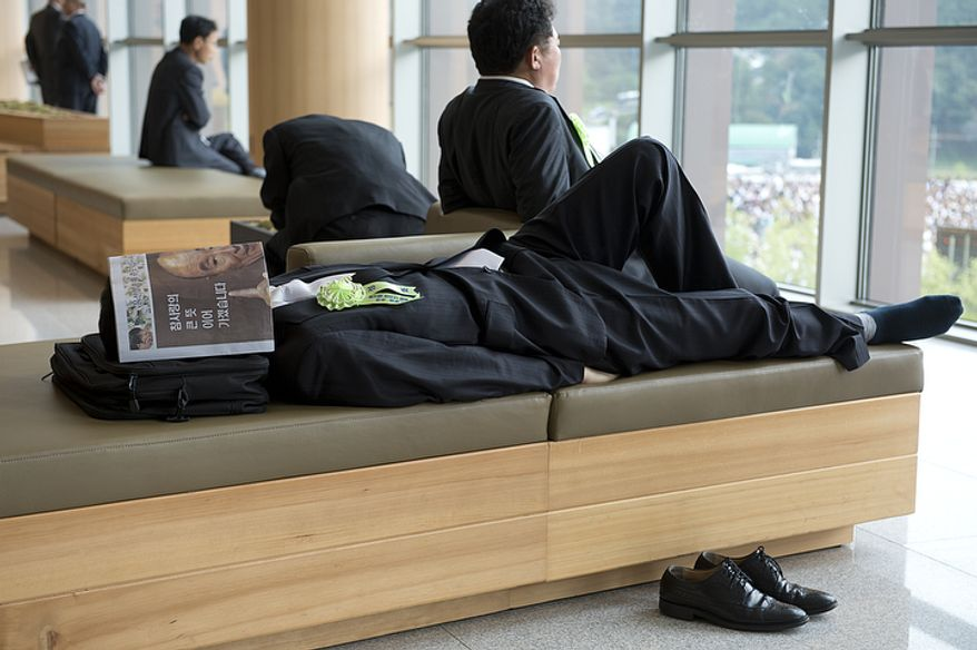 A man takes a nap with a newspaper bearing the face of the late Rev. Sun Myung Moon covering his own face in the corridor of the stadium of the Cheong Shim Peace World Center in Gapyeong, Korea on Saturday, Sept. 15, 2012, the day of the Seonghwa, or ascension, ceremony, for the reverend. (Barbara L. Salisbury/The Washington Times)