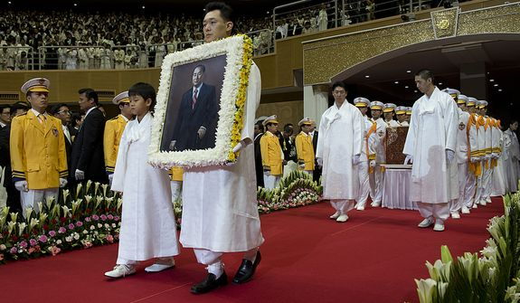 Grandson Shin Jun, left, and Kwon Jin Moon, one of the sons of the late Rev. Sun Myung Moon, carry in a portrait of the reverend at the beginning of the Seonghwa, or ascension, ceremony, known as the traditional funeral in western terms, Saturday, Sept. 15, 2012 at the Cheong Shim Peace World Center in Gapyeong, Korea. Behind them, brothers Kook Jin and Hyung Jin lead the casket in. (Barbara L. Salisbury/The Washington Times)