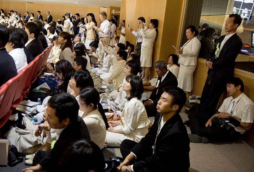 Mourners sit on the floor of the stadium on order to witness the Seonghwa, or ascension, ceremony, for the late Rev. Sun Myung Moon on Saturday, Sept. 15, 2012 at the Cheong Shim Peace World Center in Gapyeong, Korea. Some 15,000 people fit into the stadium, where the funeral was held, with another 10,000 to 15,000 expected to be watching live simulcasts around the complex. (Barbara L. Salisbury/The Washington Times)