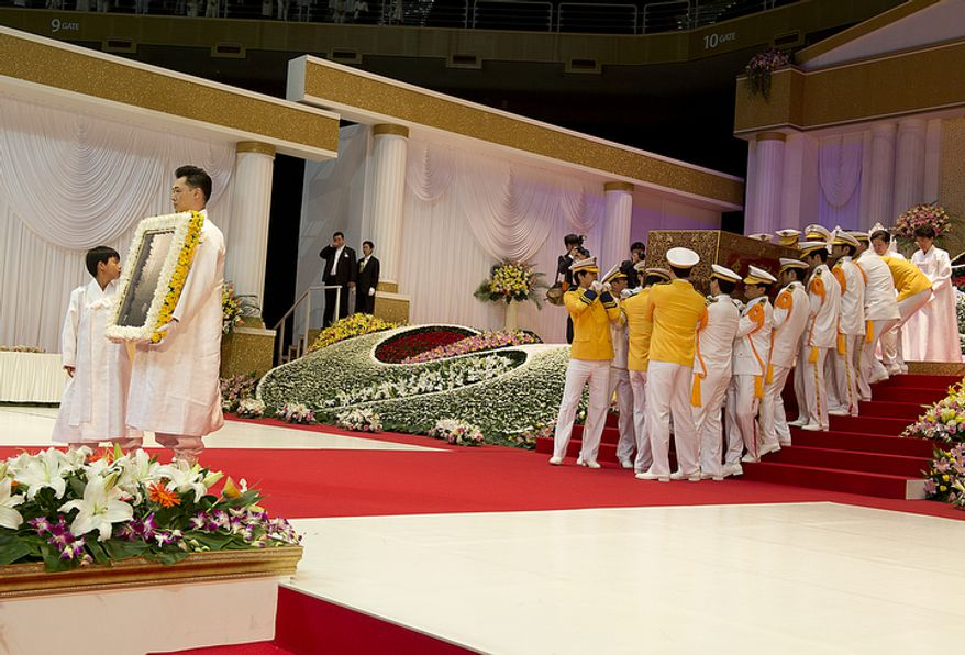 Grandson Shin Jun, left, and Kwon Jin Moon, one of the sons of the late Rev. Sun Myung Moon, carry a portrait of the reverend as the process out of the stadium at the end of the Seonghwa, or ascension, ceremony, on Saturday, Sept. 15, 2012 at the Cheong Shim Peace World Center in Gapyeong, Korea. Behind them comes the reverend's casket. (Barbara L. Salisbury/The Washington Times)