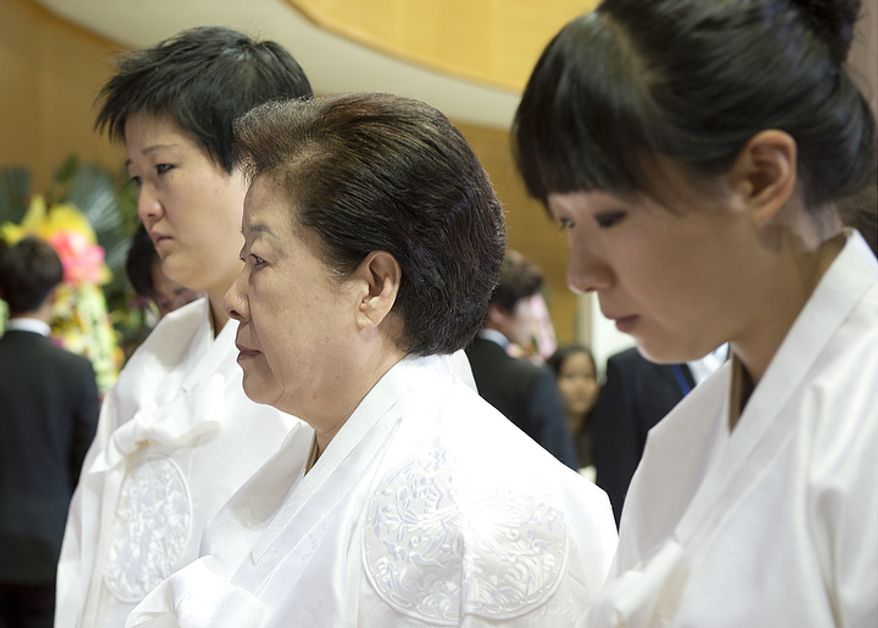 Mrs. Moon, center, is escorted out of the stadium by her two youngest daughters following the funeral for her husband, the late Rev. Sun Myung Moon, on Saturday, Sept. 15, 2012 at the Cheong Shim Peace World Center in Gapyeong, Korea. (Barbara L. Salisbury/The Washington Times)