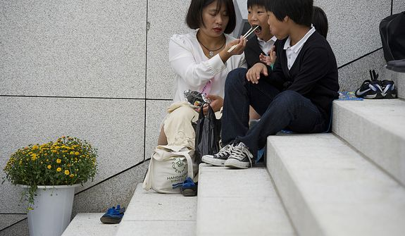 A mother feeds her children on the steps of the stadium outside the Cheong Shim Peace World Center in Gapyeong, Korea on Saturday, Sept. 15, 2012. Because thousands of mourners from countries around the world came to witness the event and say goodbye to the head of the Unification Church, the late Rev. Sun Myung Moon, many arrived very early and took a break to eat once there. (Barbara L. Salisbury/The Washington Times)