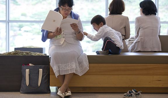 A little boy tries to get this older woman's attention as she is reading the program for the funeral for the late Rev. Sun Myung Moon inside the stadium of the Cheong Shim Peace World Center in Gapyeong, Korea on Saturday, Sept. 15, 2012. (Barbara L. Salisbury/The Washington Times)