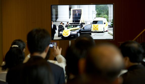 Mourners watch on a screen as the cars carrying the family and casket of the late Rev. Sun Myung Moon leave the palace to make their way to the stadium for the Seonghwa, or ascension, ceremony on Saturday, Sept. 15, 2012 at the Cheong Shim Peace World Center in Gapyeong, Korea. (Barbara L. Salisbury/The Washington Times)