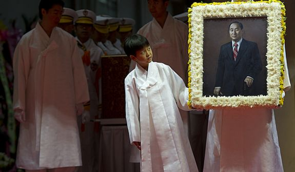 Grandson Shin Jun, left, and Kwon Jin Moon, one of the sons of the late Rev. Sun Myung Moon, carry in a portrait of the reverend at the beginning of the Seonghwa, or ascension, ceremony, known as the traditional funeral in western terms, Saturday, Sept. 15, 2012 at the Cheong Shim Peace World Center in Gapyeong, Korea. Thousands of mourners from countries around the world came to witness the event and say goodbye to the head of the Unification Church. Some 15,000 fit into the stadium, where the funeral was held, with another 10,000 to 15,000 expected to be watching live simulcasts around the complex. (Barbara L. Salisbury/The Washington Times)