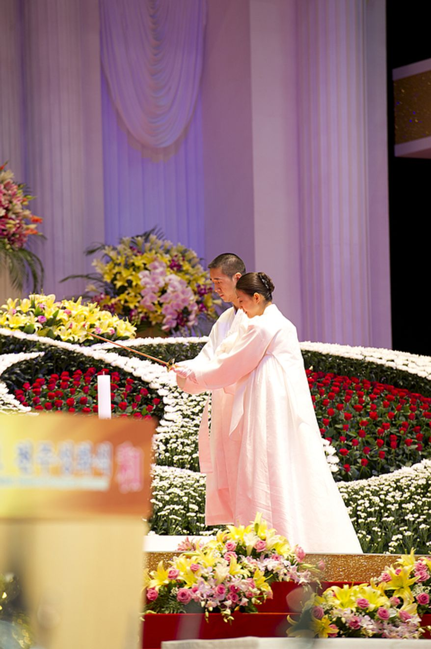 Hyung Jin Moon, left, and his wife light candles during the funeral service for Hyung Jin's father, the late Rev. Sun Myung Moon, on Saturday, Sept. 15, 2012 at the Cheong Shim Peace World Center in Gapyeong, Korea. (Barbara L. Salisbury/The Washington Times)