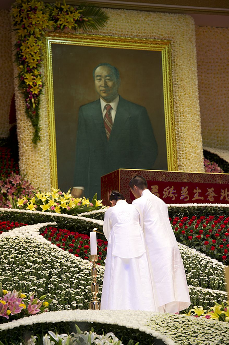 Hyung Jin Moon and his wife light candles during the funeral service for Hyung Jin's father, the late Rev. Sun Myung Moon, on Saturday, Sept. 15, 2012 at the Cheong Shim Peace World Center in Gapyeong, Korea. (Barbara L. Salisbury/The Washington Times)