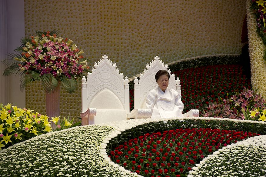 """Mrs. Moon sits in one of two seats reserved for the """"True Parents,"""" the other one obviously empty, during her husband, the late Rev. Sun Myung Moon's, funeral on Saturday, Sept. 15, 2012 at the Cheong Shim Peace World Center in Gapyeong, Korea. (Barbara L. Salisbury/The Washington Times)"""