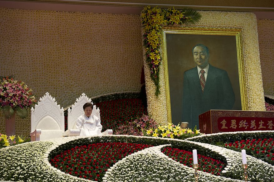 """Mrs. Moon sits in one of two seats reserved for the """"True Parents,"""" with the other one being empty, during the Seonghwa, or ascension, ceremony, known as the traditional funeral in western terms, for the late Rev. Sun Myung Moon on Saturday, Sept. 15, 2012 at the Cheong Shim Peace World Center in Gapyeong, Korea. Thousands of mourners from countries around the world came to witness the event and say goodbye to the head of the Unification Church. Some 15,000 fit into the stadium, where the funeral was held, with another 10,000 to 15,000 expected to be watching live simulcasts around the complex. (Barbara L. Salisbury/The Washington Times)"""