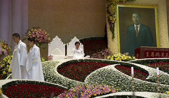 "At left, Hyung Jin Moon, son of the late Rev. Sun Myung Moon, and his wife exit the stage after lighting candles while Mrs. Moon sits in one of the chairs reserved for the ""True Parents"" during the funeral service for her husband on Saturday, Sept. 15, 2012 at the Cheong Shim Peace World Center in Gapyeong, Korea. (Barbara L. Salisbury/The Washington Times)"