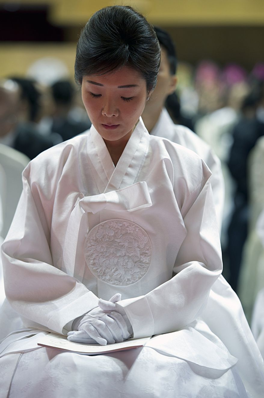 Sun Jun Moon, daughter of the late Rev. Sun Myung Moon, sits with her head down during her father's funeral at the Cheong Shim Peace World Center in Gapyeong, Korea on Saturday, Sept. 15, 2012. (Barbara L. Salisbury/The Washington Times)