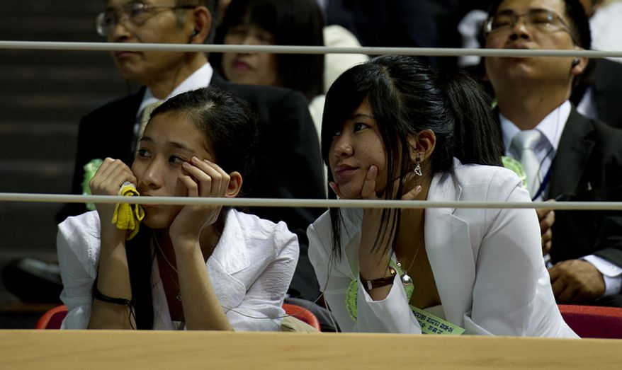 Two girls watch the video honoring the life of the Rev. Sun Myung Moon during the reverend's funeral at the Cheong Shim Peace World Center in Gapyeong, Korea on Saturday, Sept. 15, 2012. (Barbara L. Salisbury/The Washington Times)