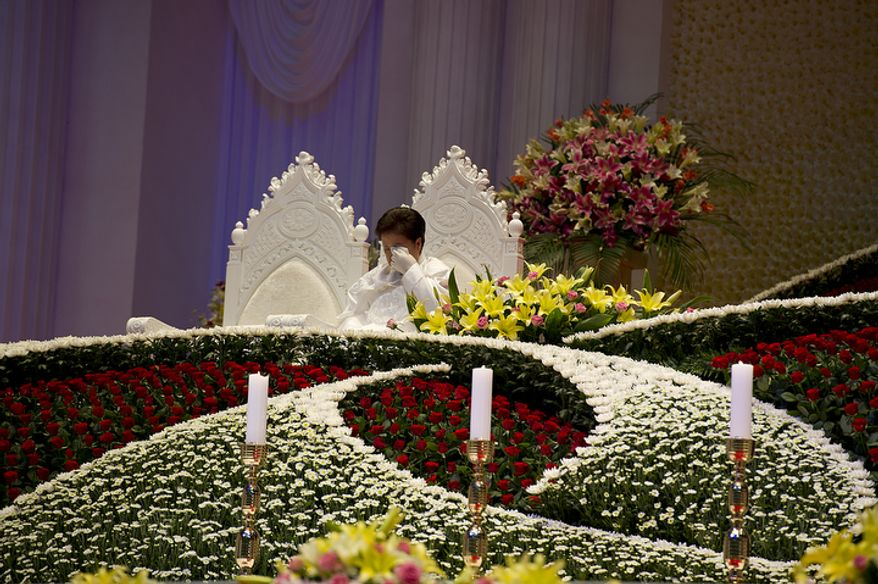 "Mrs. Moon, sitting in one of the two seats reserved for the ""True Parents,"" wipes her eyes during the funeral service for her late husband, the Rev. Sun Myung Moon, on Saturday, Sept. 15, 2012 at the Cheong Shim Peace World Center in Gapyeong, Korea. (Barbara L. Salisbury/The Washington Times)"