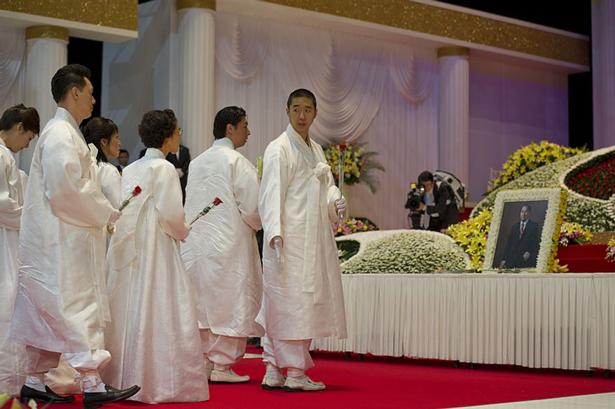Hyung Jin Moon, right, signals to his family members where they should stand to offer flowers to the late Rev. Sun Myung Moon during his funeral service Saturday, Sept. 15, 2012 at the Cheong Shim Peace World Center in Gapyeong, Korea. (Barbara L. Salisbury/The Washington Times)