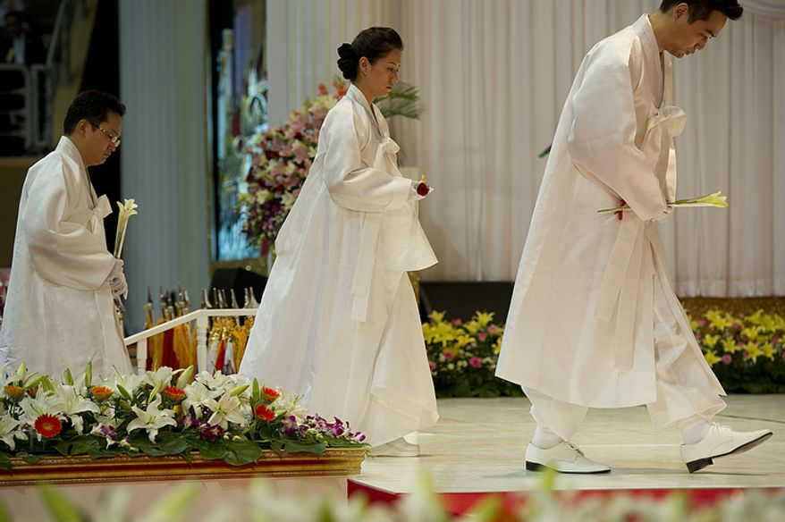 Family members of the late Rev. Sun Myung Moon walk up on stage to offer flowers during the reverend's funeral service on Saturday, Sept. 15, 2012 at the Cheong Shim Peace World Center in Gapyeong, Korea. (Barbara L. Salisbury/The Washington Times)