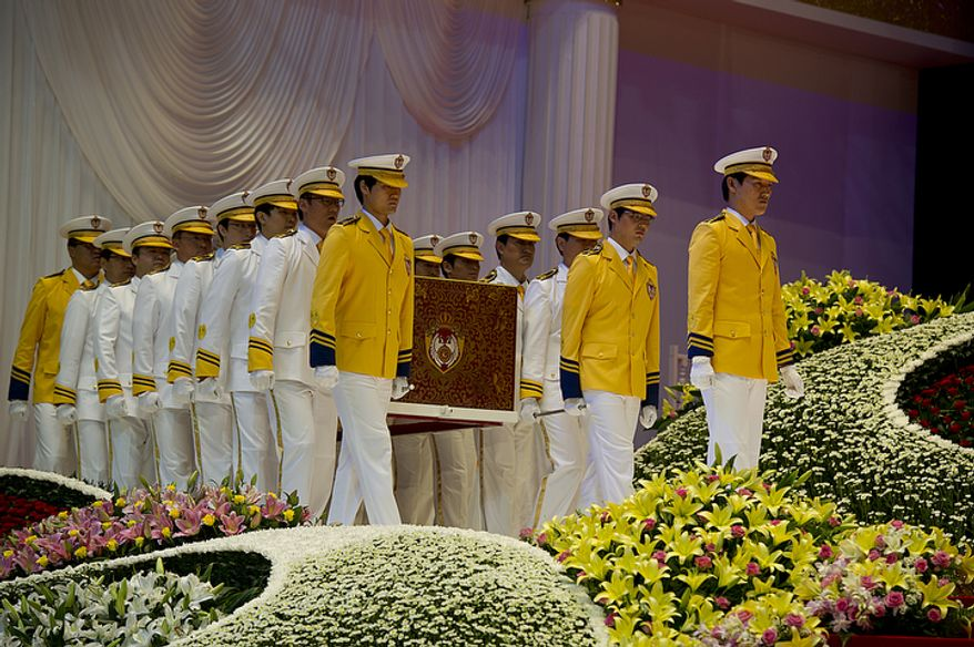 Pallbearers carry the casket of the late Rev. Sun Myung Moon as they prepare to process out of the stadium at the end of the reverend's funeral service on Saturday, Sept. 15, 2012 at the Cheong Shim Peace World Center in Gapyeong, Korea. (Barbara L. Salisbury/The Washington Times)