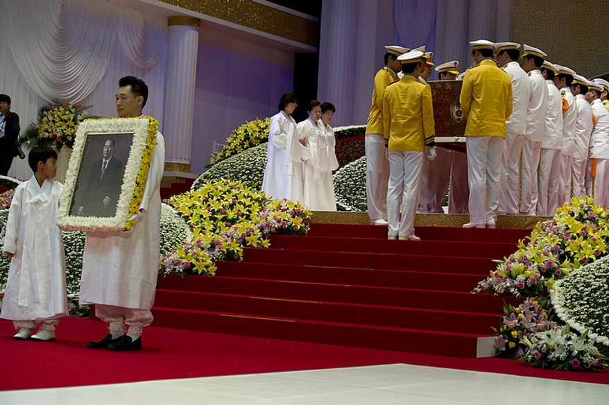 Grandson Shin Jun, left, and Kwon Jin Moon, one of the sons of the late Rev. Sun Myung Moon, carrying a portrait of the reverend, wait for the casket and Mrs. Moon before processing out of the stadium at the end of the Seonghwa, or ascension, ceremony, for the reverend Saturday, Sept. 15, 2012 at the Cheong Shim Peace World Center in Gapyeong, Korea. Behind them, brothers Kook Jin and Hyung Jin lead the casket in. (Barbara L. Salisbury/The Washington Times)