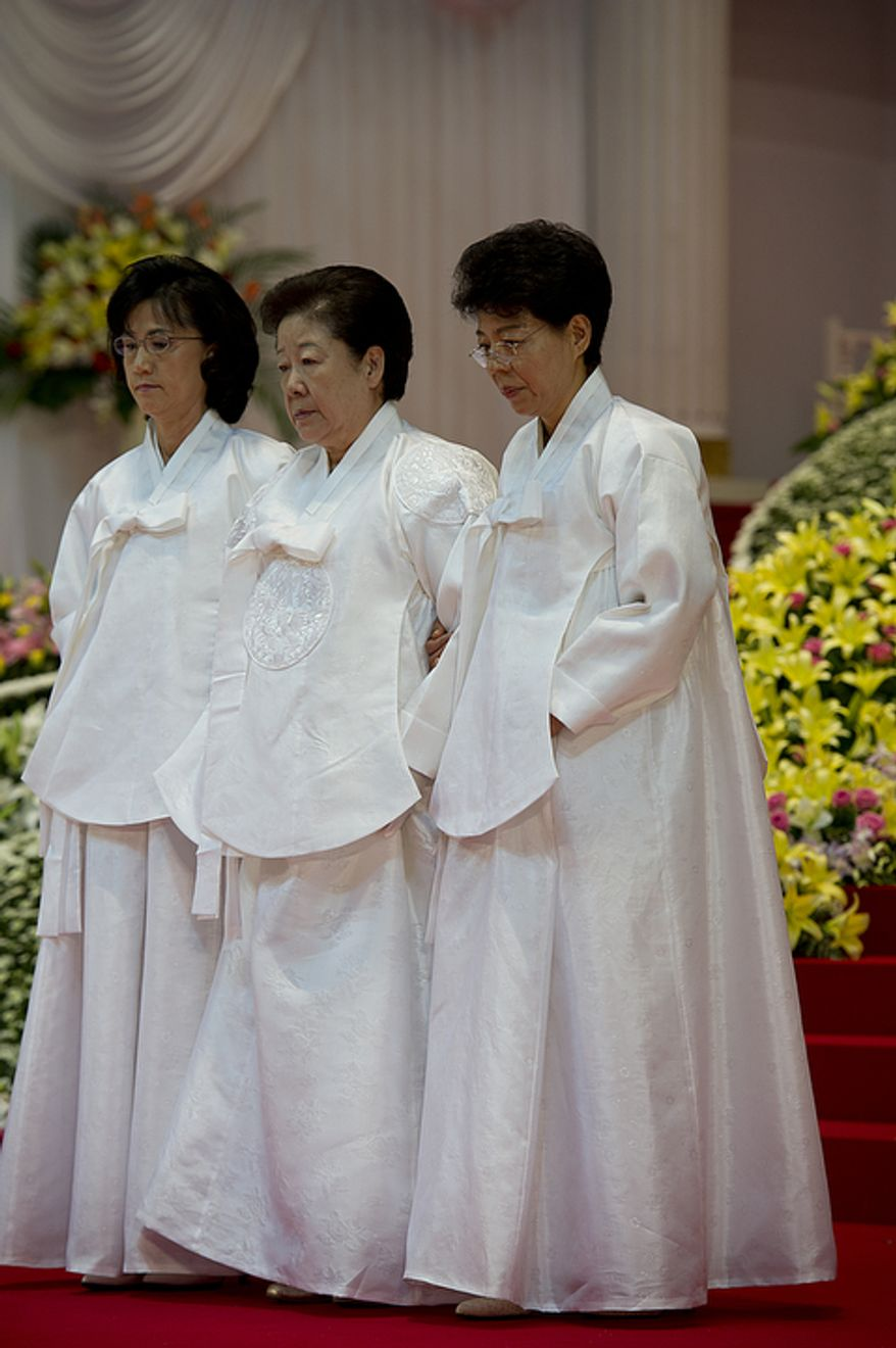Mrs. Moon, center, is escorted out of the stadium following the funeral service for her husband, the late Rev. Sun Myung Moon, on Saturday, Sept. 15, 2012 at the Cheong Shim Peace World Center in Gapyeong, Korea. (Barbara L. Salisbury/The Washington Times)