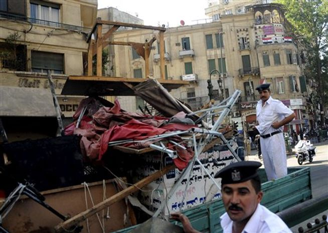 Egyptian police load furniture and other items confiscated from street vendors as they clear Tahrir Square in Cairo, Egypt, Saturday, Sept. 15, 2012, after days of protest
