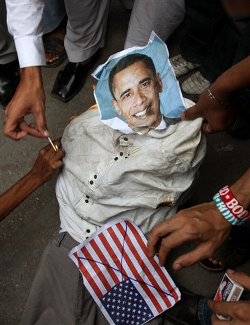 Supporters of a Insaf Student Federation burn an effigy of U.S. President Barack Obama and a representation of a U.S. flag demonstration in Karachi, Pakistan, on Saturday, Sept. 15, 2012, as part of widespread anger across the Muslim world about a film ridiculing Islam's Prophet Muhammad. (AP Photo/Fareed Khan)