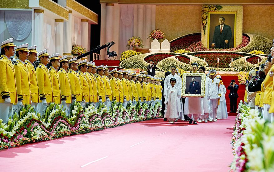 Members of the Moon family, including grandson Shin Jun (left) and Kwon Jin Moon, a son of the Rev. Sun Myung Moon, carry portrait of the Unification Church leader after the ascension ceremony Saturday for the reverend, who died Sept. 2 in Gapyeong, Korea. Lining the walkway are members of second-generation church families. (Barbara L. Salisbury/The Washington Times)
