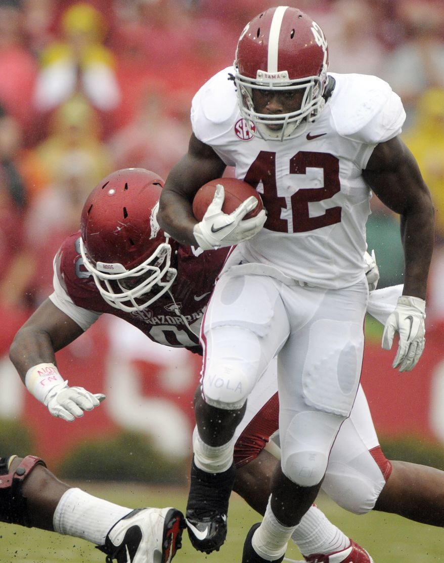 Alabama running back Eddie Lacy (42) eludes Arkansas defensive tackle Robert Thomas during the first half of an NCAA college football game in Fayetteville, Ark., Saturday, Sept. 15, 2012. (AP Photo/David Quinn)