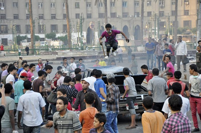 An Egyptian protester stomps on the roof of a car in Tahrir Square in Cairo, Egypt, early Saturday, Sept. 15, 2012, before police cleared the area after days of protests against a film ridiculing the Prophet Muhammad. Egyptian police on Saturday cleared out protesters who have been clashing wit