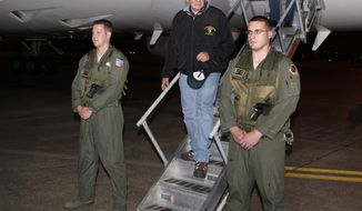 Defense Secretary Leon E. Panetta (center) steps off his jet after arriving at Yokota Air Base on the outskirts of Tokyo on Sunday, Sept. 16, 2012. Mr. Panetta is in Japan as part of an Asian tour, which includes stops in China and New Zealand. (AP Photo/Larry Downing, Pool)