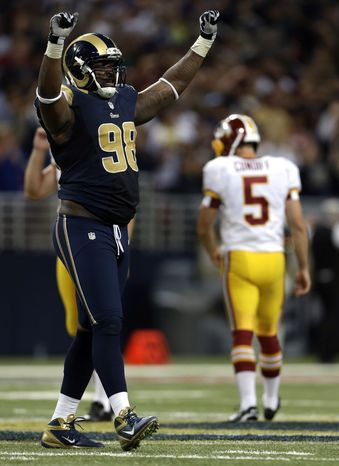 St. Louis Rams' Kendall Langford, left, celebrates after Washington Redskins kicker Billy Cundiff, right, missed a 62-yard field goal-attempt during the fourth quarter of an NFL football game on Sunday, Sept. 16, 2012, in St. Louis. The Rams won 31-28. (AP Photo/Jeff Roberson)