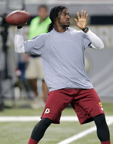 Washington Redskins quarterback Robert Griffin III warms up before the start of an NFL football game between the St. Louis Rams and the Washington Redskins Sunday, Sept. 16, 2012, in St. Louis