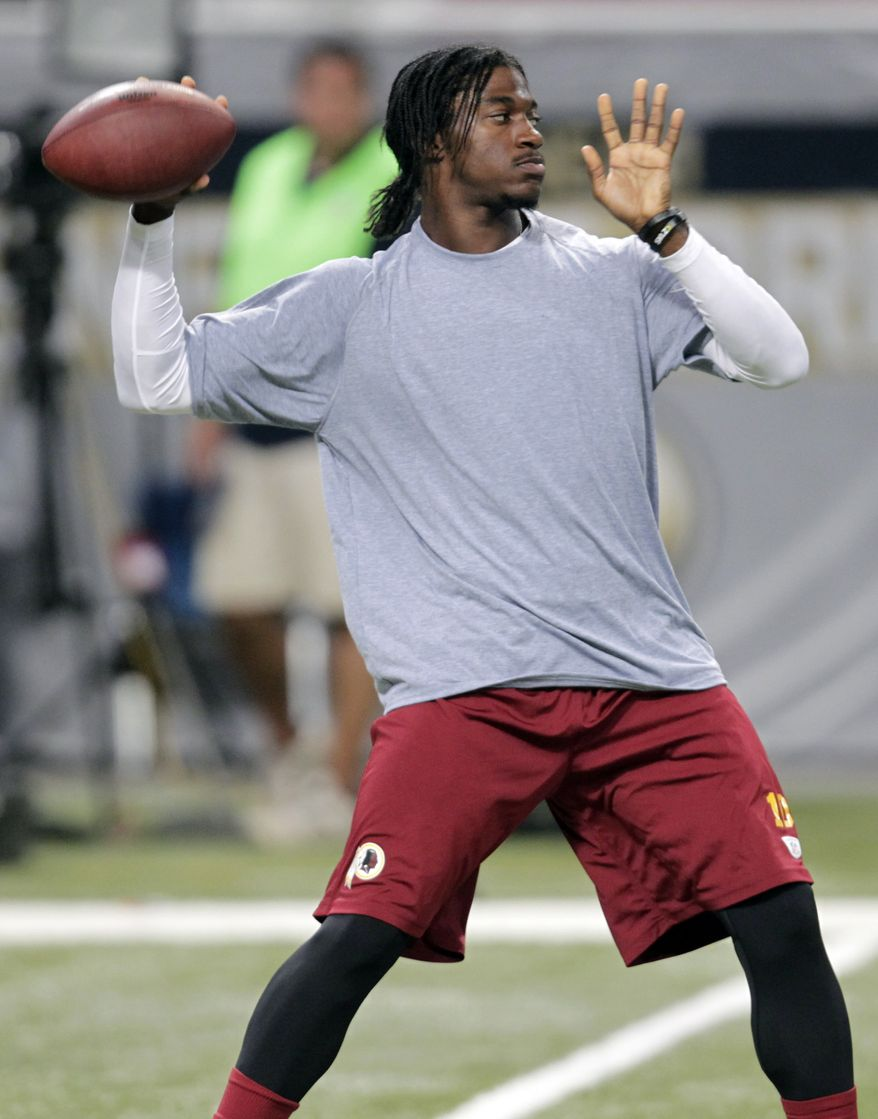 Washington Redskins quarterback Robert Griffin III warms up before the start of an NFL football game between the St. Louis Rams and the Washington Redskins Sunday, Sept. 16, 2012, in St. Louis. (AP Photo/Tom Gannam)