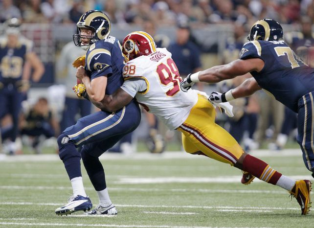 St. Louis Rams quarterback Sam Bradford, left, is fumbles as he is sacked by Washington Redskins outside linebacker Brian Orakpo during the first quarter. (AP Photo/Tom Gannam)