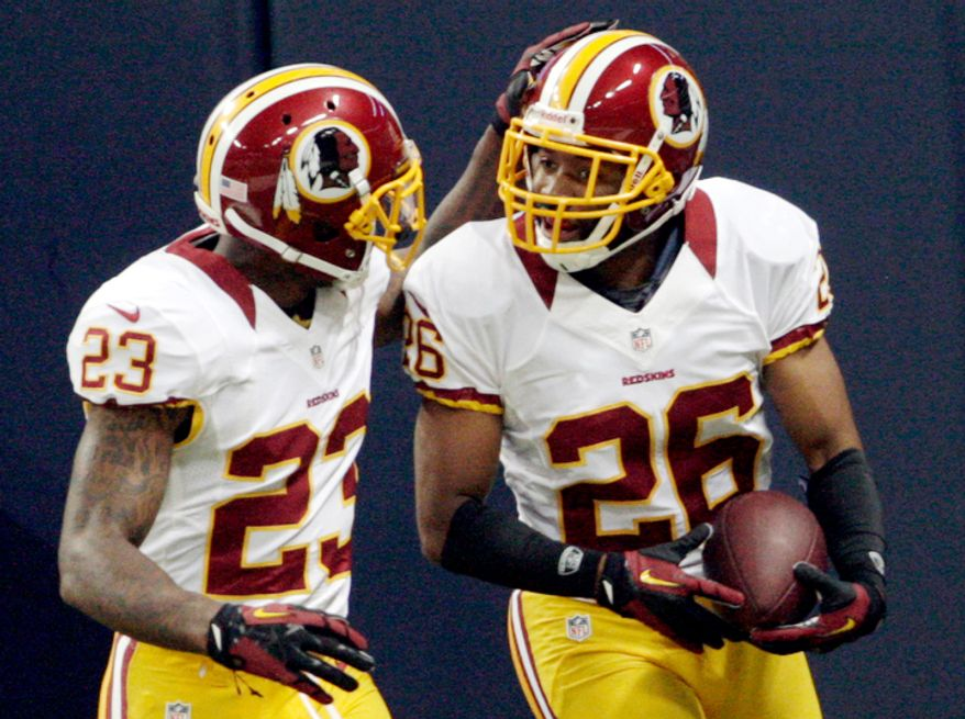 Washington Redskins cornerback Josh Wilson, right, is congratulated by DeAngelo Hall after running a fumble back for a touchdown during the first quarter. (AP Photo/Tom Gannam)