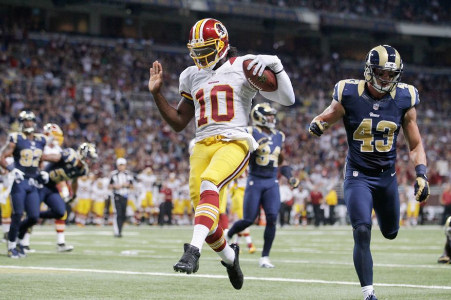 Washington Redskins quarterback Robert Griffin III, left, scores on a 5-yard run past St. Louis Rams strong safety Craig Dahl during the first quarter. (AP Photo/Seth Perlman)