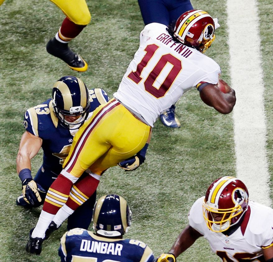 Washington Redskins quarterback Robert Griffin III (10) heads for the end zone past St. Louis Rams strong safety Craig Dahl, left, on a touchdown run during the third quarter. (AP Photo/Jeff Roberson)