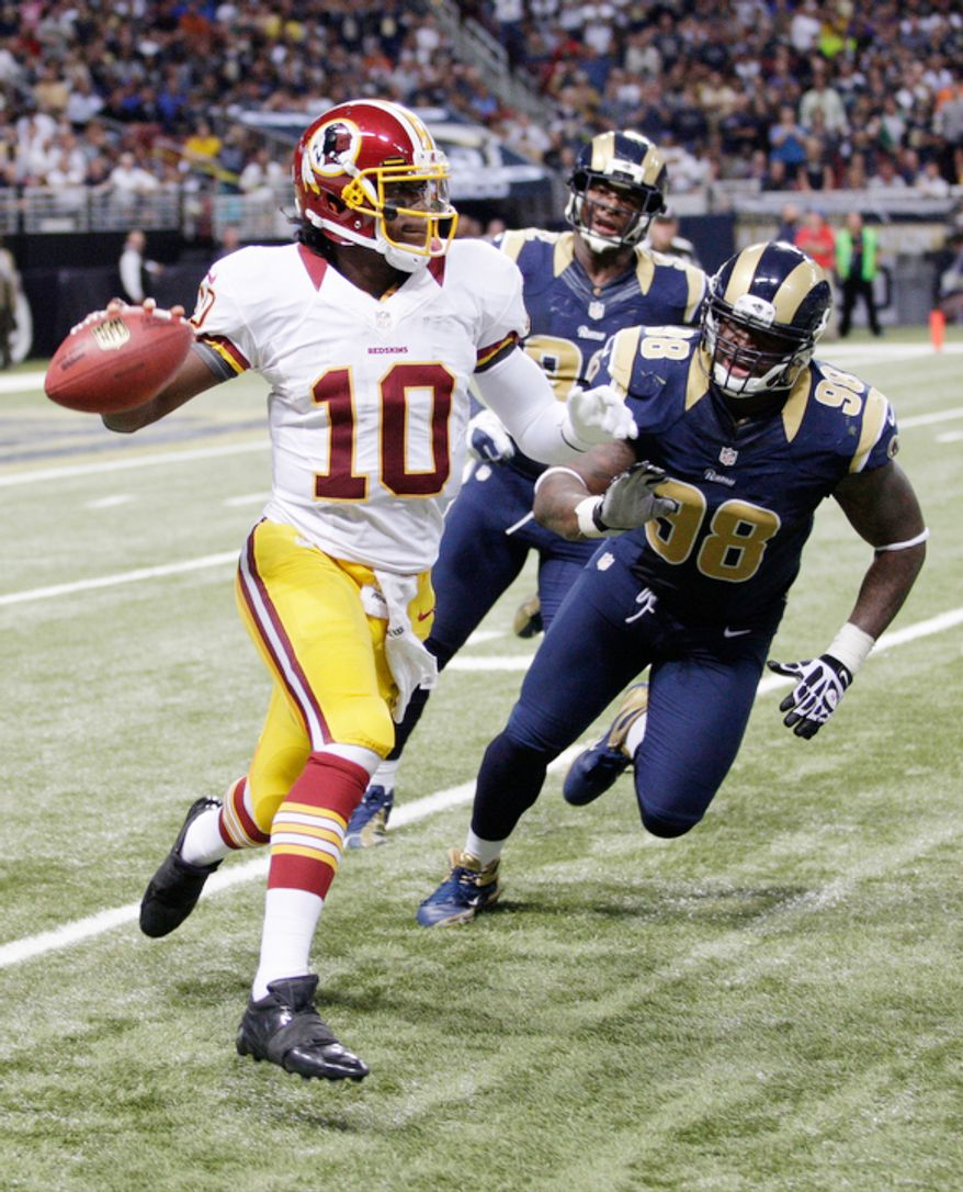 Washington Redskins quarterback Robert Griffin III, left, throws as St. Louis Rams defensive end Eugene Sims, center, and defensive tackle Kendall Langford give chase during the fourth quarter. The Rams won 31-28. (AP Photo/Tom Gannam)