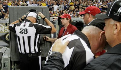 Referee Wayne Elliott (28) prepares to review a play during the fourth quarter. (AP Photo/Seth Perlman)
