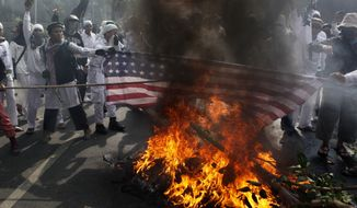 """Muslim protesters burn a U.S. flag during a demonstration against the American-made film """"Innocence of Muslims,"""" which ridicules Islam and depicts the Prophet Muhammad as a fraud, a womanizer and a madman, outside the U.S. Embassy in Jakarta, Indonesia, on Monday, Sept. 17, 2012. (AP Photo/Dita Alangkara)"""